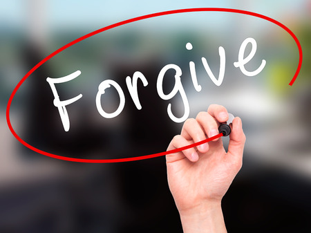 redeeming: Man Hand writing Forgive with black marker on visual screen. Isolated on office. Business, technology, internet concept. Stock Image