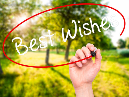 farewell party: Man Hand writing Best Wishes  with black marker on visual screen. Isolated on nature. Business, technology, internet concept. Stock Photo