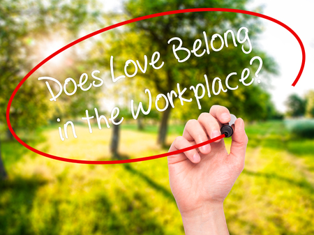 belong: Man Hand writing Does Love Belong in the Workplace? with black marker on visual screen. Isolated on nature. Business, technology, internet concept. Stock Photo Stock Photo