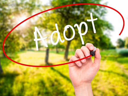 adopting: Man Hand writing Adopt  with black marker on visual screen. Isolated on nature. Business, technology, internet concept. Stock Photo