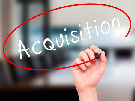 acquiring: Man Hand writing Acquiring with black marker on visual screen. Isolated on office. Business, technology, internet concept. Stock Image