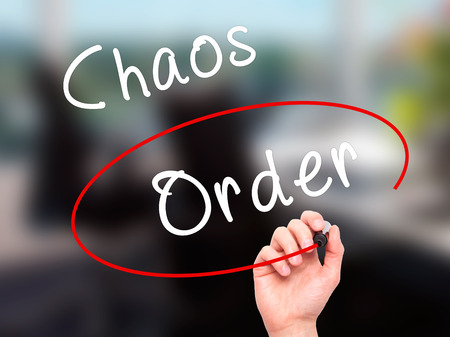 chaos order: Man Hand writing and Choosing Order instead of Chaos with black marker on visual screen. Isolated on office. Business, technology, internet concept. Stock Image