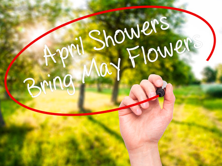 april showers: Man Hand writing April Showers Bring May Flowers with black marker on visual screen. Isolated on nature. Business, technology, internet concept. Stock Photo Stock Photo