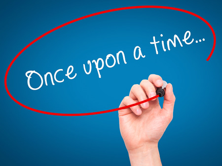 phrase novel: Man Hand writing Once upon a time... with black marker on visual screen. Isolated on blue. Business, technology, internet concept. Stock Image Stock Photo