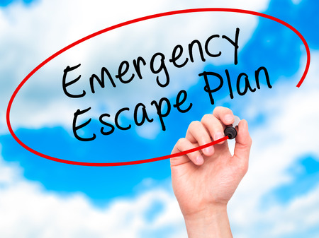 emergency plan: Man Hand writing Emergency Escape Plan with black marker on visual screen. Isolated on sky. Business, technology, internet concept. Stock Image