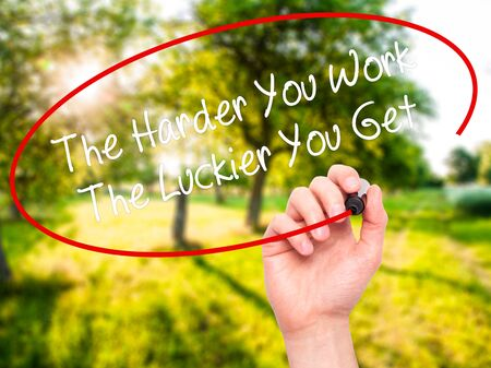 harder: Man Hand writing The Harder You Work The Luckier You Get  with black marker on visual screen. Isolated on nature. Business, technology, internet concept. Stock Photo
