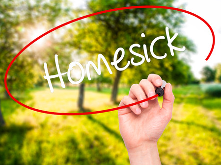 hankering: Man Hand writing Homesick with black marker on visual screen. Isolated on nature. Business,  internet concept. Stock Photo Stock Photo