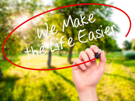 easier: Man Hand writing We Make the Life Easier with black marker on visual screen. Isolated on nature. Business, technology, internet concept. Stock Photo