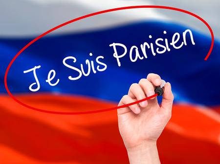 writing on screen: Man Hand writing Je Suis Parisien with black marker on visual screen. Isolated on flag. Stock Photo