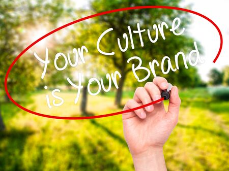 identidad cultural: Man Hand writing Your Culture is Your Brand with black marker on visual screen. Isolated on nature. Business, technology, internet concept. Stock Photo
