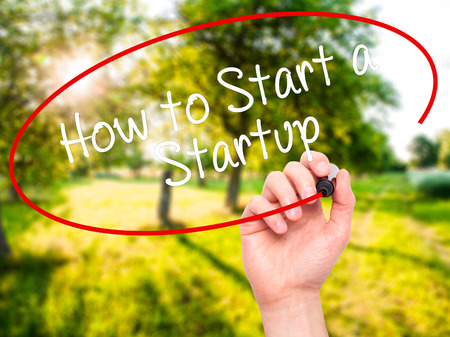 sucessful: Man Hand writing How to Start a Startup with black marker on visual screen. Isolated on background. Business, technology, internet concept. Stock Photo