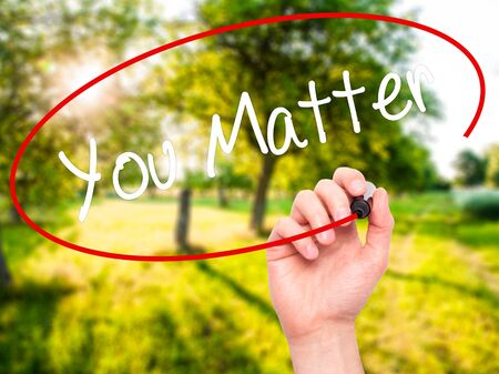 matter: Man Hand writing You Matter with black marker on visual screen. Isolated on nature. Business, technology, internet concept. Stock Photo
