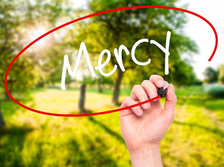 absolution: Man Hand writing Mercy with black marker on visual screen. Isolated on nature. Business, technology, internet concept. Stock Photo