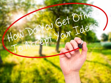 persuasiveness: Man Hand writing How Do You Get Others To Accept Your Ideas? with black marker on visual screen. Isolated on nature. Business, technology, internet concept. Stock Photo
