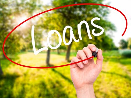 business loans: Man Hand writing Loans  with black marker on visual screen. Isolated on background. Business, technology, internet concept. Stock Photo
