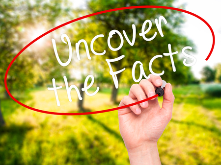 factual: Man Hand writing Uncover the Facts with black marker on visual screen. Isolated on nature. Business, technology, internet concept. Stock Image