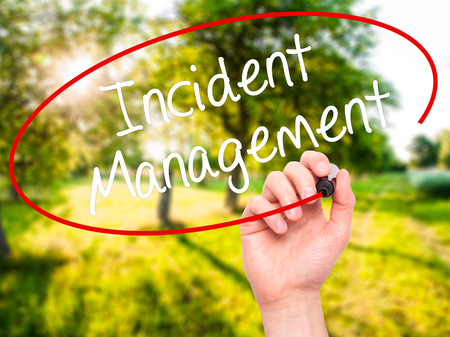 drp: Man Hand writing Incident Management with black marker on visual screen. Isolated on nature. Business, technology, internet concept. Stock Photo