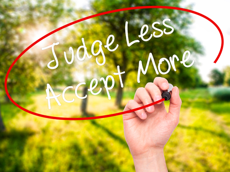unfavorable: Man Hand writing Judge Less Accept More with black marker on visual screen. Isolated on background. Business, technology, internet concept. Stock Photo