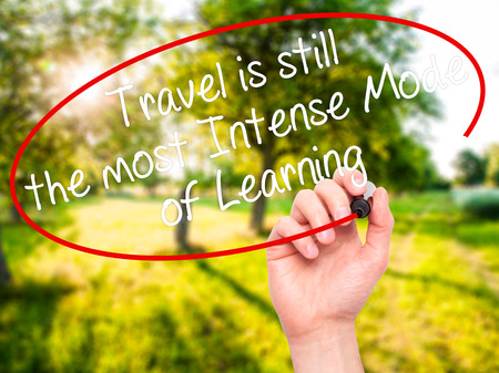 self discovery: Man Hand writing Travel is still the most Intense Mode of Learning with black marker on visual screen. Isolated on background. Business, technology, internet concept. Stock Photo Stock Photo