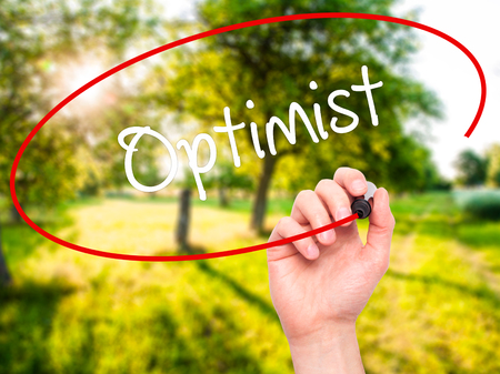 optimist: Man Hand writing Optimist  with black marker on visual screen. Isolated on nature. Business, technology, internet concept. Stock Photo