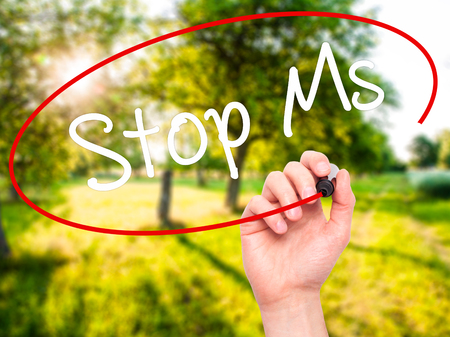 ms: Man Hand writing Stop Ms with black marker on visual screen. Isolated on nature. Business, technology, internet concept. Stock Photo
