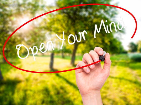 open minded: Man Hand writing Open Your Mind with black marker on visual screen. Isolated on background. Business, technology, internet concept. Stock Photo Stock Photo