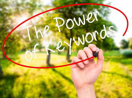 Man Hand writing The Power of Keywords with black marker on visual screen. Isolated on nature. Business, technology, internet concept. Stock Photo
