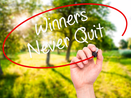 persevere: Man Hand writing Winners Never Quit with black marker on visual screen. Isolated on background. Business, technology, internet concept. Stock Photo