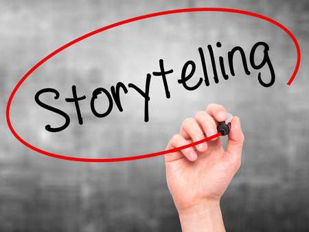 storytelling: Man Hand writing Storytelling  with black marker on visual screen. Isolated on background. Business, technology, internet concept. Stock Photo