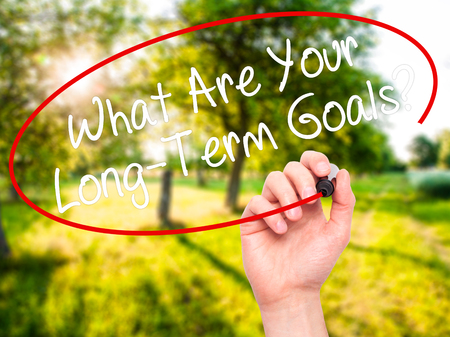 longterm: Man Hand writing What Are Your Long-Term Goals? with black marker on visual screen. Isolated on nature. Business, technology, internet concept. Stock Photo