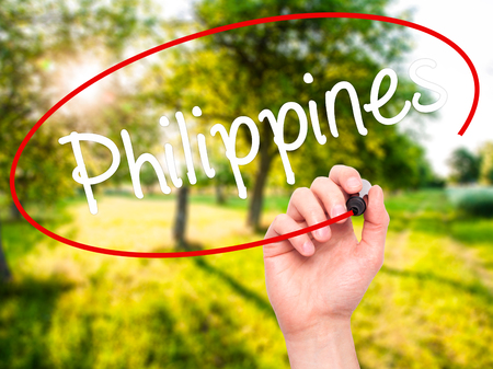 Man Hand writing Philippines with black marker on visual screen. Isolated on nature. Business, technology, internet concept. Stock Photo