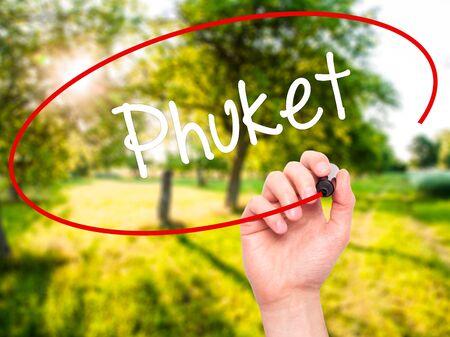 phuket province: Man Hand writing Phuket with black marker on visual screen. Isolated on nature. Business, technology, internet concept. Stock Photo
