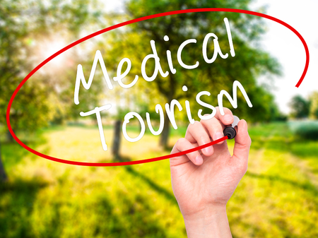 health care fees: Man Hand writing Medical Tourism with black marker on visual screen. Isolated on nature. Business, technology, internet concept. Stock Photo Stock Photo