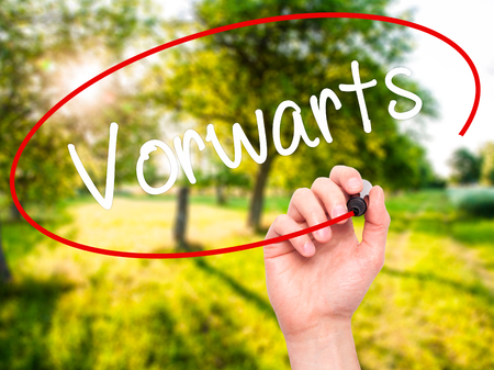 next horizon: Man Hand writing Vorw??¤rts  (Forward In German)  with black marker on visual screen. Isolated on nature. Business, technology, internet concept. Stock Photo