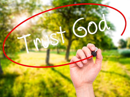 trust in god: Man Hand writing Trust God  with black marker on visual screen. Isolated on nature. Business, technology, internet concept. Stock Photo Stock Photo