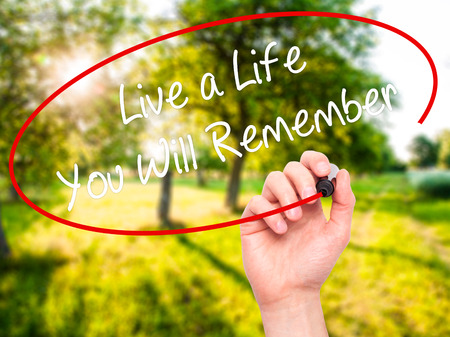 Man Hand writing Live a Life You Will Remember with black marker on visual screen. Isolated on nature. Business, technology, internet concept.