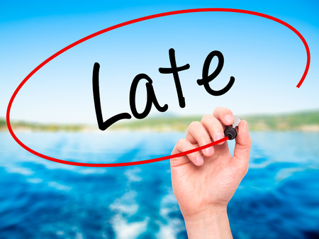 lateness: Man Hand writing Late with black marker on visual screen. Isolated on background. Business, technology, internet concept. Stock Photo