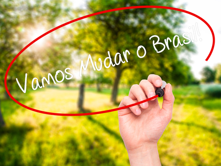 protestors: Man Hand writing Vamos Mudar o Brasil! (Lets Change Brazil in Portuguese)  with black marker on visual screen. Isolated on nature. Business, technology, internet concept. Stock Photo Stock Photo