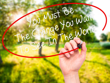 helping others: Man Hand writing You Must Be The Change You Want To See In The World with black marker on visual screen. Isolated on nature. Business, technology, internet concept. Stock Photo