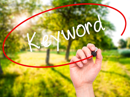 spamdexing: Man Hand writing Keyword with black marker on visual screen. Isolated on nature. Business, technology, internet concept. Stock Photo