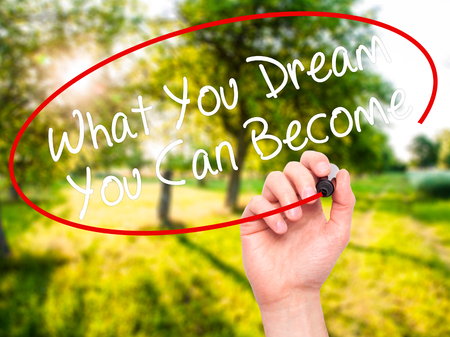 become: Man Hand writing What You Dream You Can Become with black marker on visual screen. Isolated on nature. Business, technology, internet concept. Stock Photo