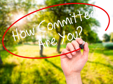 commitment committed: Man Hand writing How Committed Are You? with black marker on visual screen. Isolated on nature. Business, technology, internet concept. Stock Photo