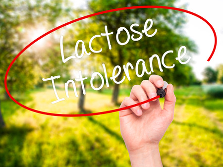 intolerance: Man Hand writing Lactose Intolerance with black marker on visual screen. Isolated on background. Business, technology, internet concept. Stock Photo