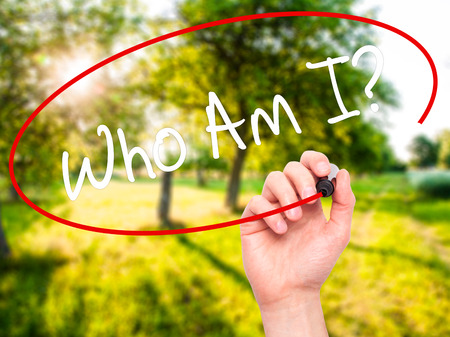 Man Hand writing Who Am I? with black marker on visual screen. Isolated on nature. Business, technology, internet concept. Stock Photo