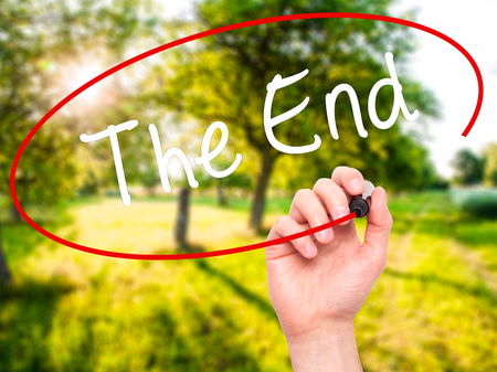 conclusive: Man Hand writing The End with black marker on visual screen. Isolated on nature. Business, technology, internet concept. Stock Photo