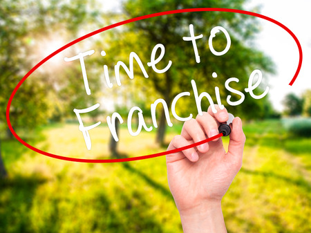 Man Hand writing Time to Franchise with black marker on visual screen. Isolated on nature. Business, technology, internet concept. Stock Photo