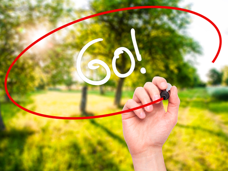 working ethic: Man Hand writing Go!  with black marker on visual screen. Isolated on nature. Business, technology, internet concept. Stock Photo