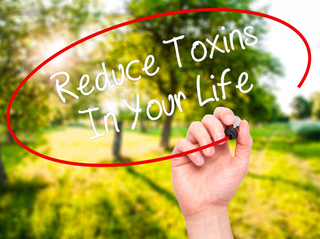 toxins: Man Hand writing Reduce Toxins In Your Life with black marker on visual screen. Isolated on nature. Business, technology, internet concept. Stock Photo