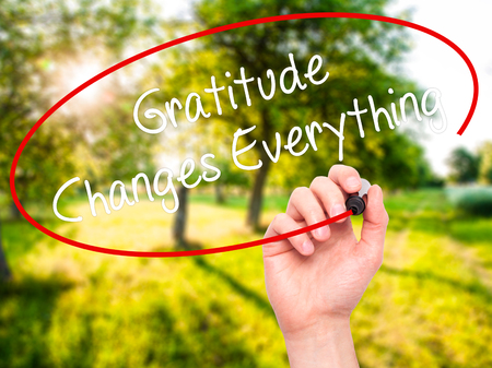 universal love: Man Hand writing Gratitude Changes Everything with black marker on visual screen. Isolated on nature. Business, technology, internet concept. Stock Photo