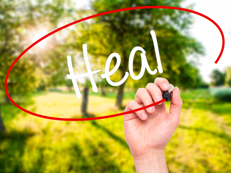complementary therapies: Man Hand writing  Heal  with black marker on visual screen. Isolated on background. Business, technology, internet concept. Stock Photo Stock Photo